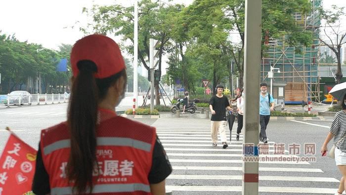图一:身披红马甲的北滘志愿者已经就位,指引市民文明出行_副本.jpg