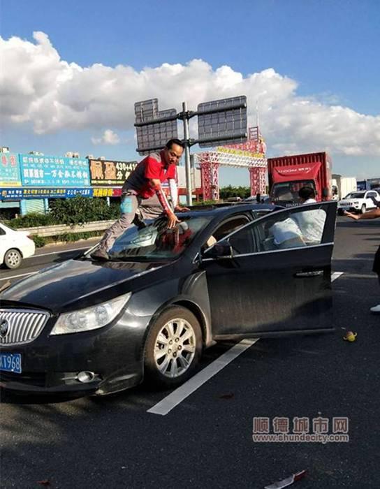 何健暖爬上小汽车车顶准备救人。.jpg